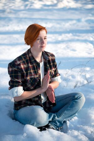 Girl resting in snowy forest in yoga pose. Beautiful young woman sitting in yoga position. Winter meditation concept.