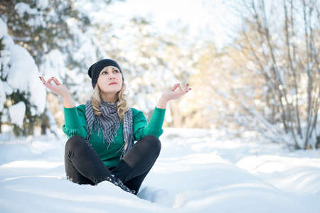 Beautiful woman sits in lotus position in frozen park. Tranquility and yoga concept with copy space.