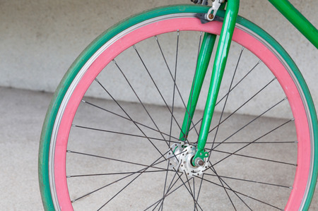 fixed: wheel of green fixed gear bicycle at building Stock Photo