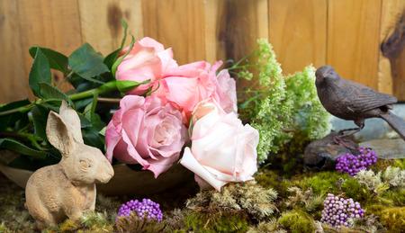 vase plaster: still life with pink of rose and Rabbit ceramic plaster  beside bird vintage iron on moss ground Stock Photo