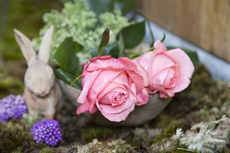 vase plaster: still life with pink of rose and Rabbit ceramic plaster on moss ground