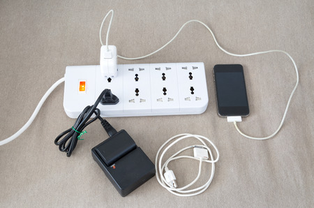 adapters: Power cord with several adapters and chargers for various electronic devices in a paperless office Stock Photo