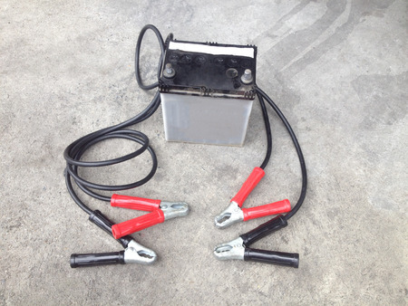 car accessory: Repair of car batteries with Car battery charger at dirty parking  Bulbs fluids and battery