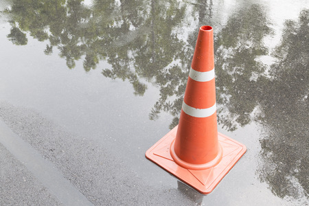 of rain: a traffic cone on the road in rain time and reflection Stock Photo