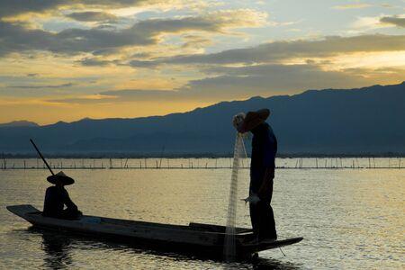 garish: Silhouette of fisherman is traditional thai fishing style,  sunset time, at Kwan Phayao lake, Phayao province, Thailand