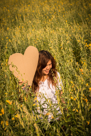 kinky: asian young women with slightly curly is holding heart symbol in yellow field at summer, vintage tone style, Thailand , vintage tone style, Thailand Stock Photo