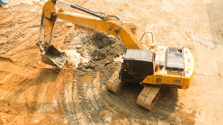 aerial view of Tracked excavator starts digging ground preparing to build condominium. track hoe working. Stok Fotoğraf
