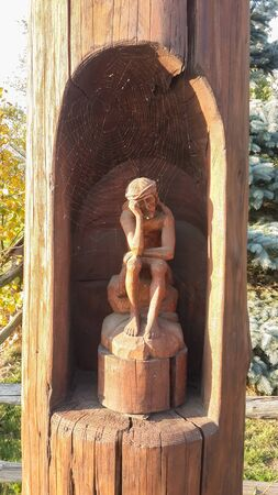 Sad man sits on the rock waiting for something covered in cobweb. Spider web over bored man wooden Statue. 版權商用圖片