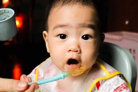 Close up of happy little seven months old son in see through plastic bib eating in chair for babies after mom made him eat avocado and banana mix.Happy baby's face. Asian infant open mouth.