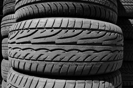 Pile of used car tires background. Black and white. photo