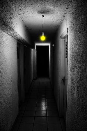gloomy: Yellow light glowing in dark underground corridor.