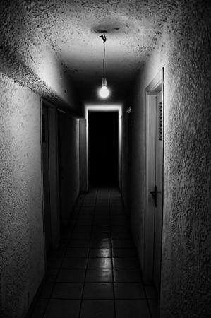 passageway: Dim light glowing in dark underground corridor.