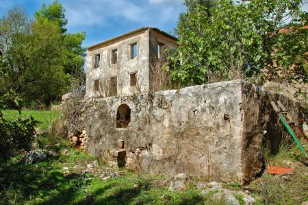 winepress: Vintage stone tank for grape stomping and derelict house ruins. Zakynthos, Greece.