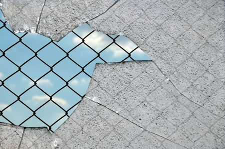 Broken glass fragments and chain link wired fence pattern against blue sky. photo