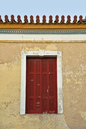 Red window shutter and weathered wall of a neoclassical building in Athens, Greece. Stock Photo - 6597564