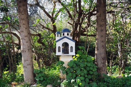 Small street church shrine surrounded by trees and plants. Athens, Greece. photo