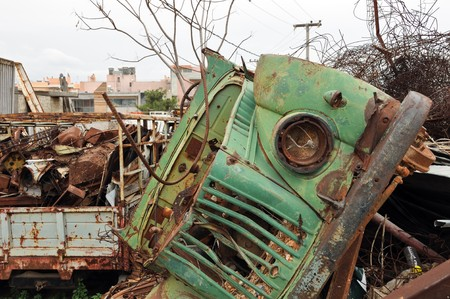 Rusty vintage car and scrap metal at a junkyard. photo