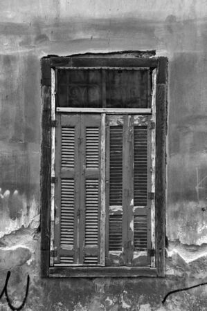 Vintage window shutters and grungy abandoned house wall. Black and white. Stock Photo - 7060018