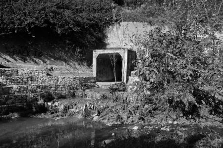 Waste water and sludge from a drain contaminating a small river. Black and white. photo