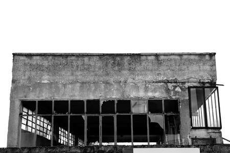 disuse: Broken windows facade of an abandoned warehouse. Black and white. Stock Photo