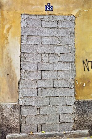 Bricked up door and weathered wall of an abandoned building. Stock Photo - 8106761