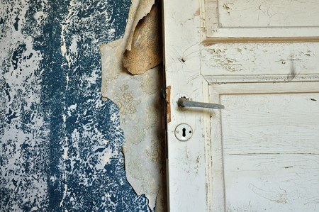 Torn vintage wallpaper peeling paint wall and wooden door in abandoned house. photo