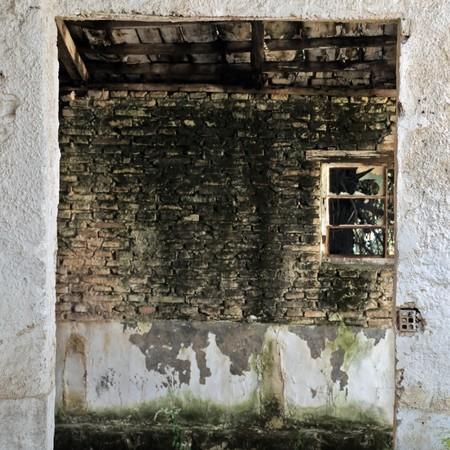 warehouse interior: Magazzino abbandonato vuoto interiore, finestra rotta e vernice scheggiato muro.