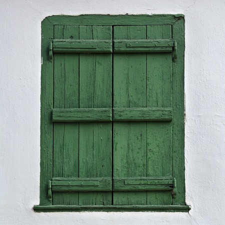 Green wooden window shutter and white wall. Stock Photo