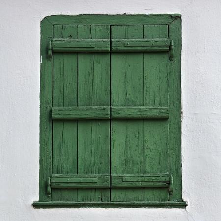 Green wooden window shutter and white wall. Stok Fotoğraf