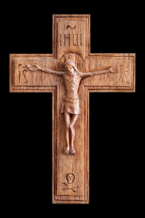 Wooden crucifix with skull and crossbones isolated on black background. photo
