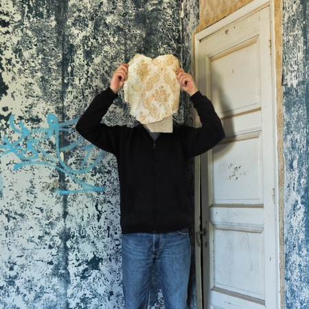 Figure obscured by torn wallpaper shred in decaying abandoned house interior. photo