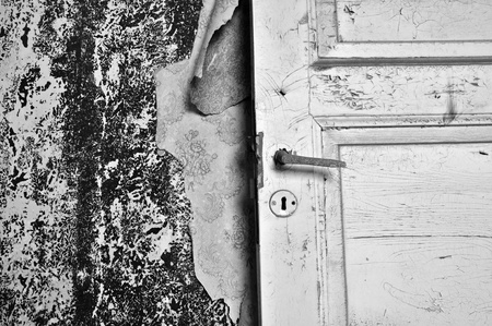 Torn wallpaper and old door in abandoned house. Black and white. photo