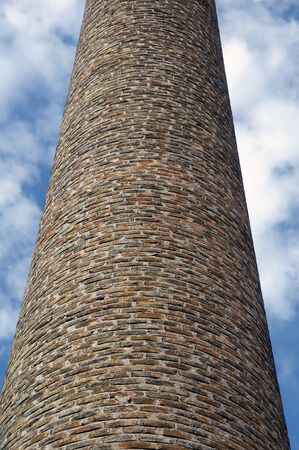 Weathered brick chimney of an old factory. Industrial architecture. photo