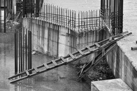 Rusty steel bars and ladders at construction site on rainy day. Black and white. photo
