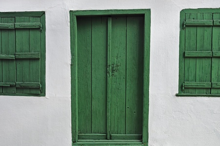 Green door wooden window shutters and white wall. photo