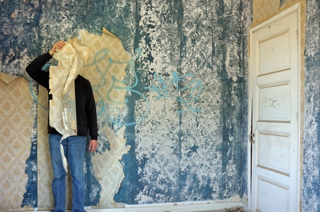 Male figure behind torn wallpaper shred in abandoned building interior. Stock Photo - 9115771