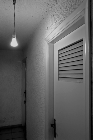 bare wire: Bare light bulb and doors in underground hallway. Black and white.