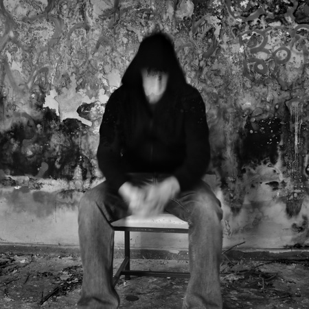 Man dissolving into textured black mold and peeling paint wall. photo
