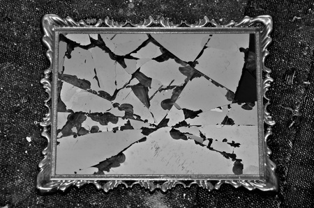 smashed: Antique picture frame with broken glass on dirty rag background. Black and white.