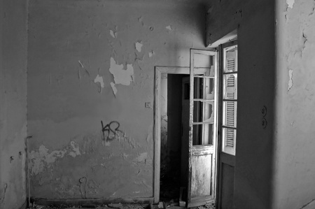Empty room and peeling paint wall in abandoned house. Black and white. photo