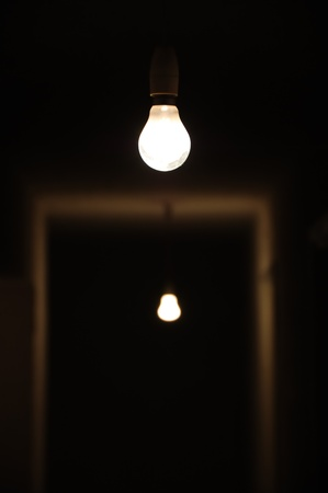 Bare light bulbs in dark underground hallway.