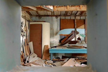 trashed: View to ramshackled room with boarded up window frame in abandoned factory. Stock Photo