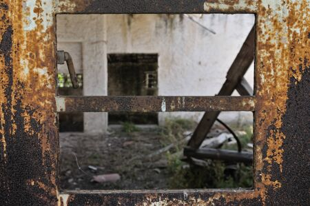 Rusty industrial door with chipped paint and view to abandoned warehouse interior. Stock Photo - 9217110
