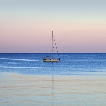 Sailboat reflections on sea water. Sunset sea and sky horizon. photo