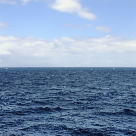 Deep open sea water and blue sky horizon.