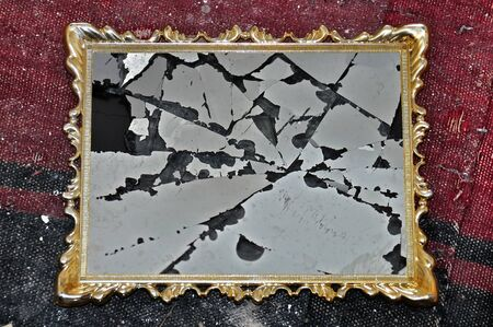 cracked glass: Antique golden picture frame with broken glass on dirty rag background.