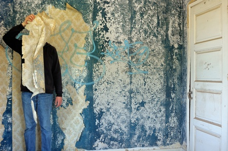 Male figure behind torn wallpaper shred in abandoned building interior. Stock Photo - 9316407