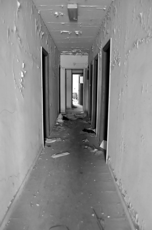 Long empty corridor and doors in abandoned building. Black and white. Stock Photo - 9316341