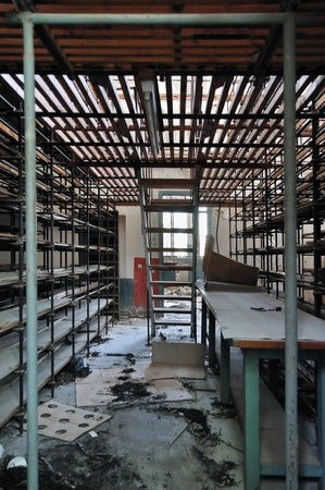 Empty shelves in abandoned vinyl records pressing factory storage room. photo