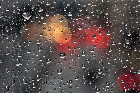 Raindrops on glass surface and blurry abstract city lights. Background texture.
